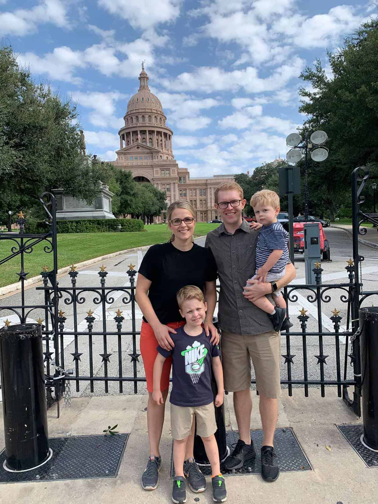 A family standing in front of the Austin Texas capitol.