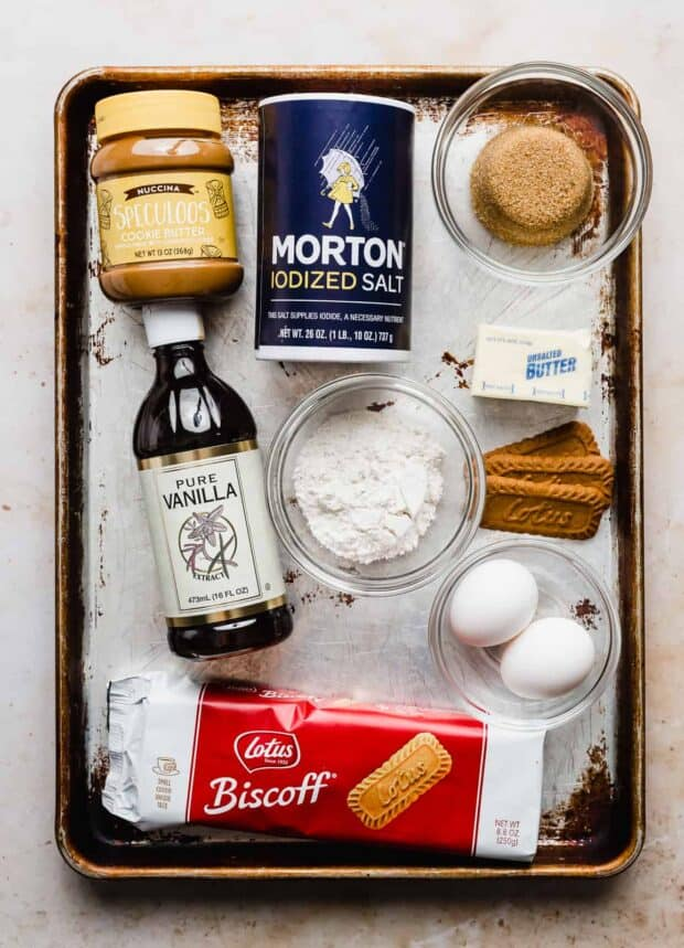 A baking tray with ingredients used to make biscoff brownies: vanilla, Biscoff cookies, salt, sugar, eggs.