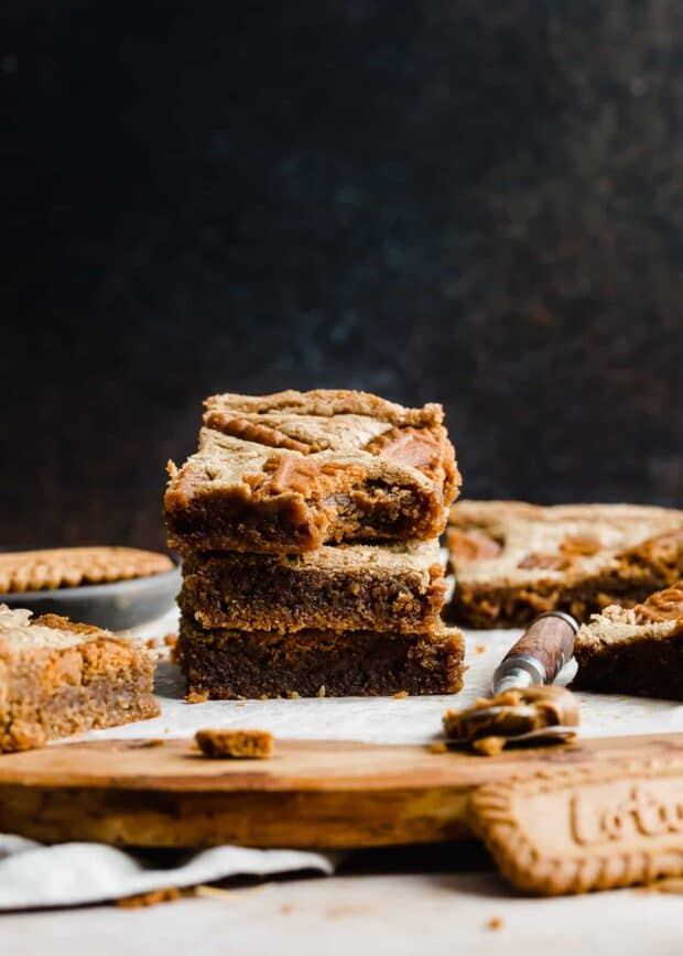 A stack of 3 Biscoff Brownies on top of each other, against a dark background.