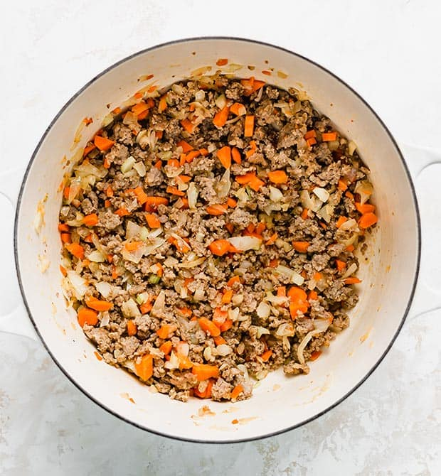 A large pot with some ground sausage, diced onion, carrots, and celery.