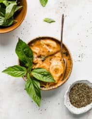 A bowl of tomato tortellini soup with a sprig of fresh basil.