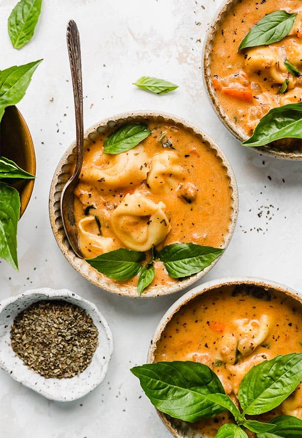 Three small bowls full of tomato tortellini soup with a fresh basil garnish.