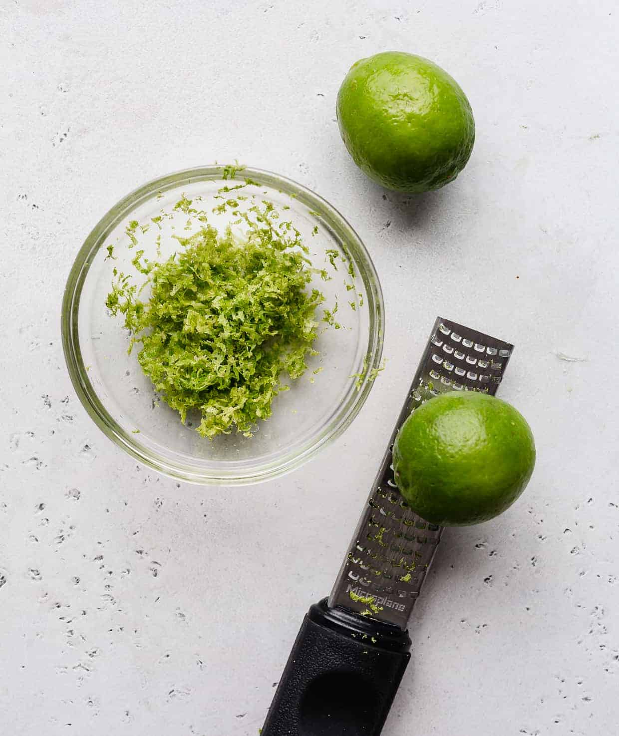 Fresh lime zest in a glass bowl.