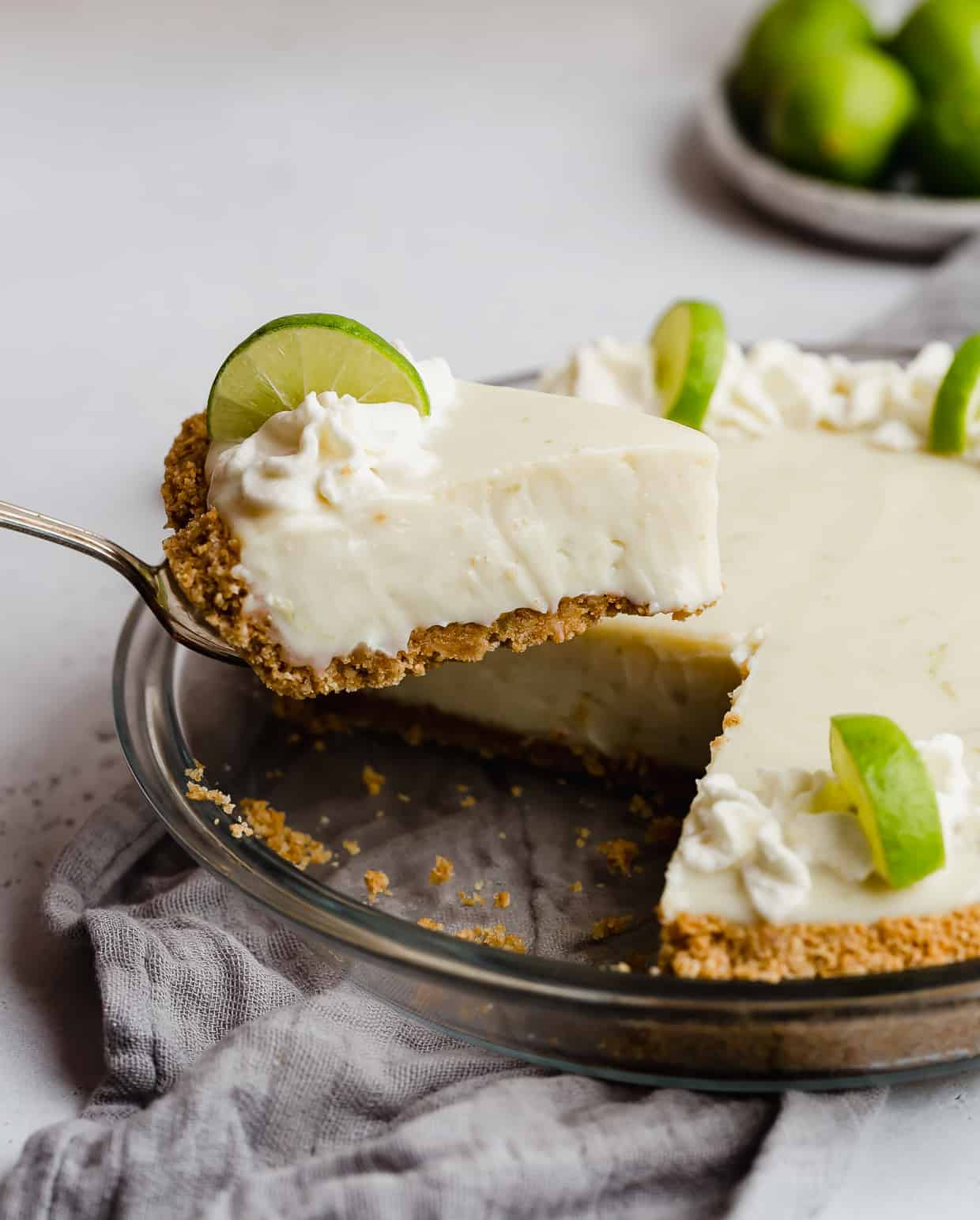 A metal spatula holding up a slice of key lime pie.