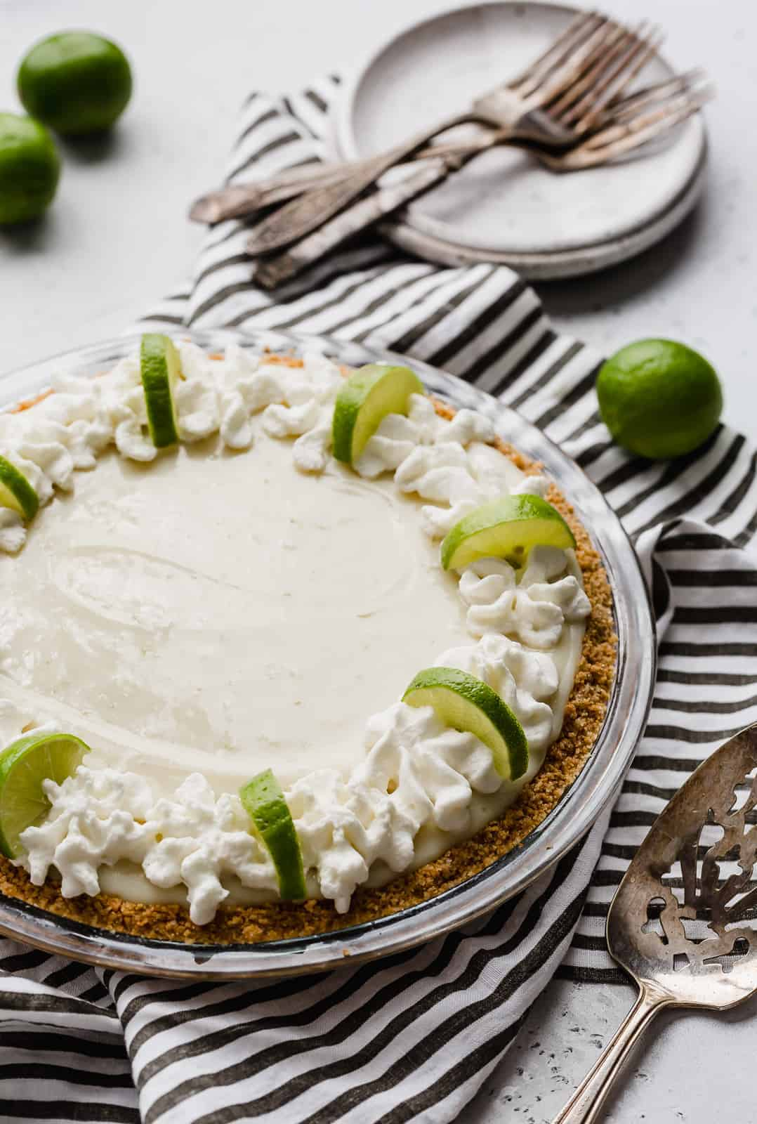 A key lime pie topped with whipped cream and lime slices.