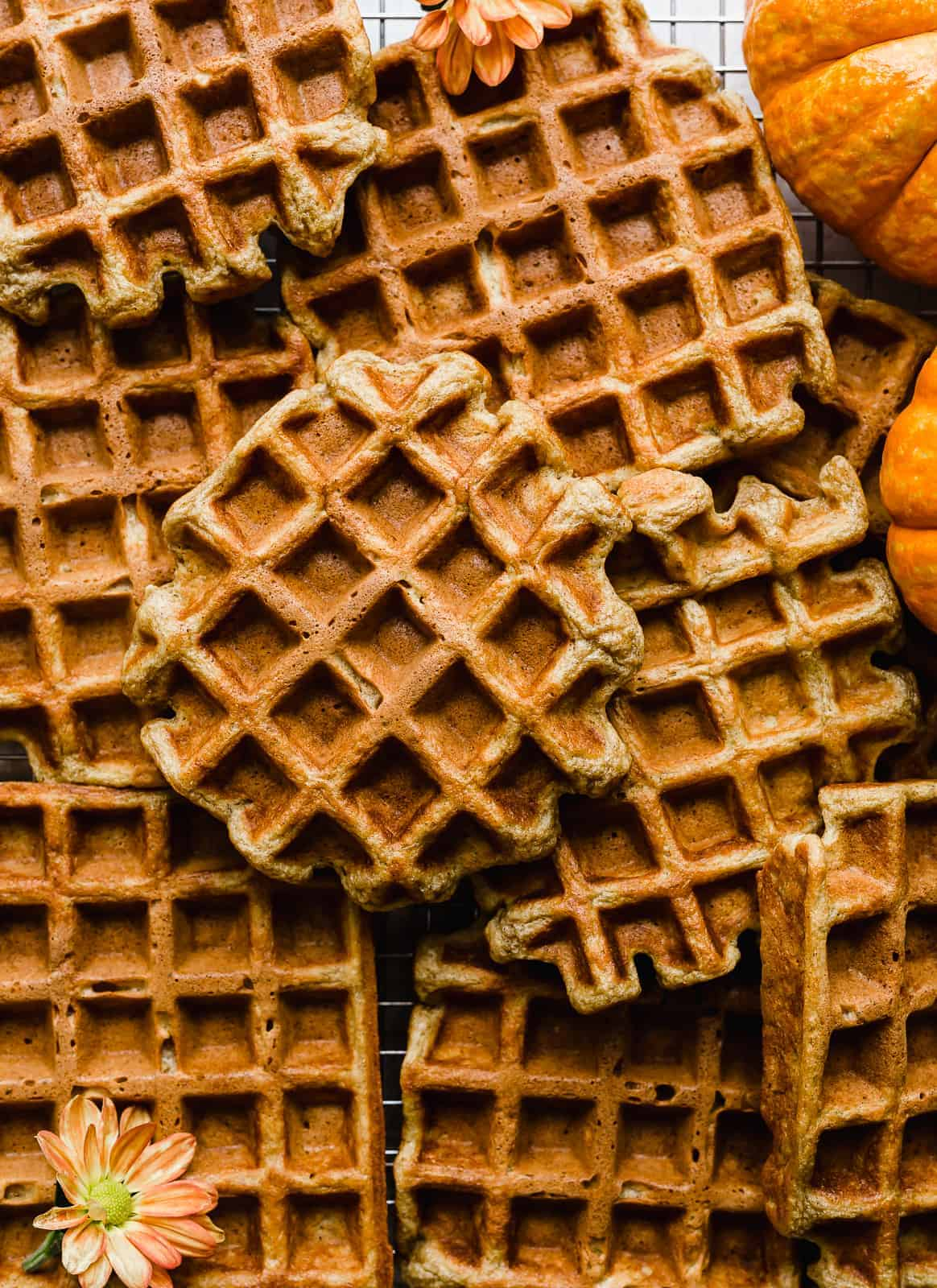 A pile of Pumpkin Waffles with mini orange pumpkins in the top right corner.