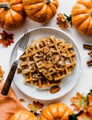 Two Pumpkin Waffles on a white plate surrounded by mini pumpkins.