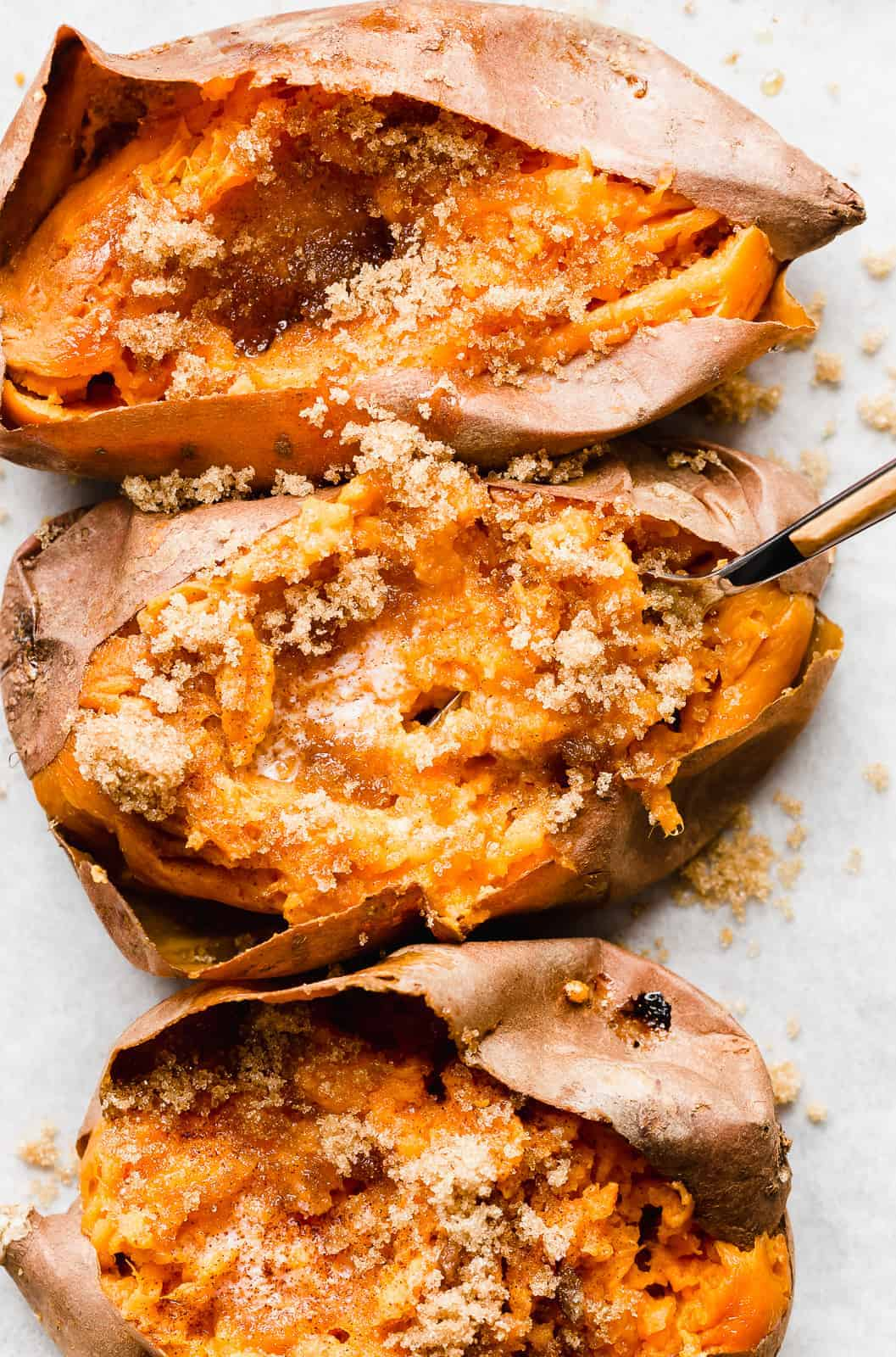 A fork scooping up some baked sweet potato.