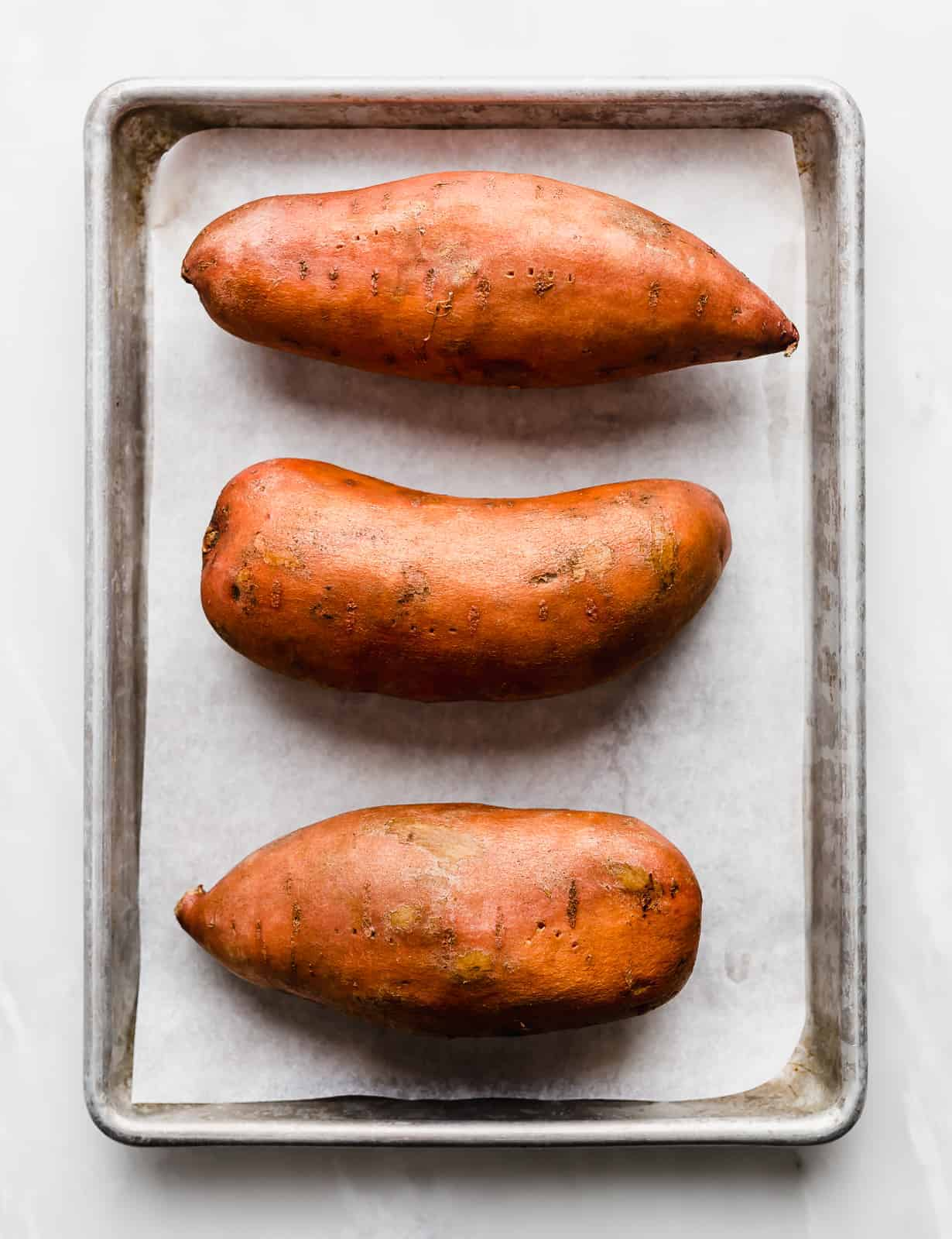 Three large sweet potatoes on a white parchment lined baking sheet.