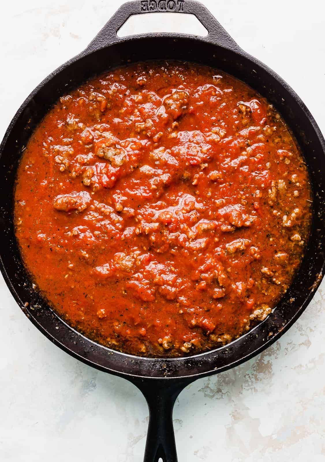 Crushed tomatoes and cooked meat in a large skillet.
