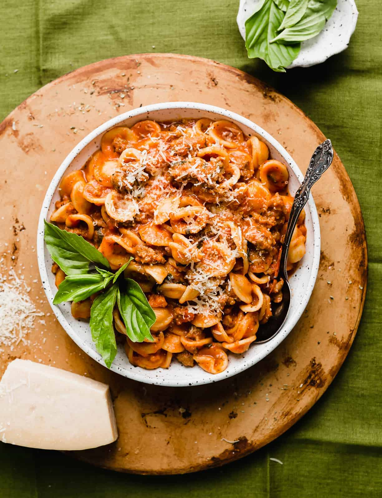 Bolognese sauce tossed with noodles, in a large white bowl.