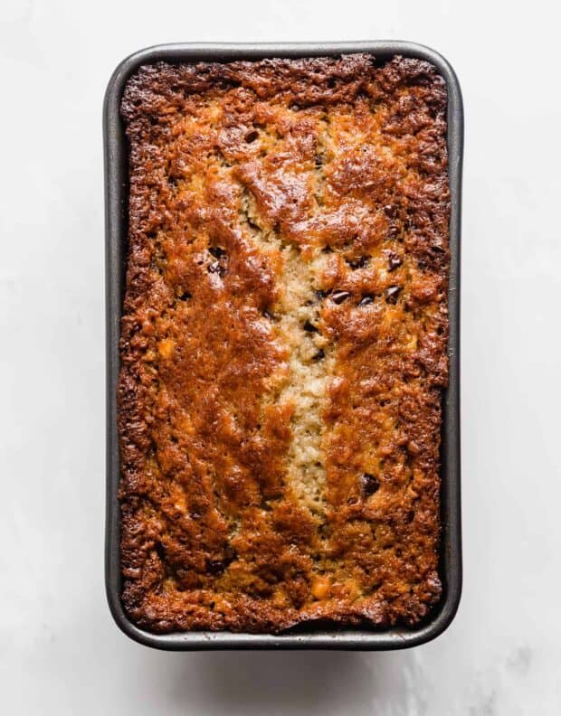 Golden brown baked Chocolate Chip Banana Bread in a loaf pan against a white background.
