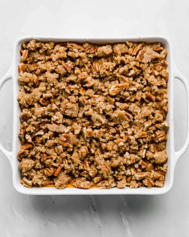 A square pan with a pecan crumble topping over sweet potato casserole.