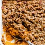 A large serving spoon scooping into a dish of sweet potato casserole.