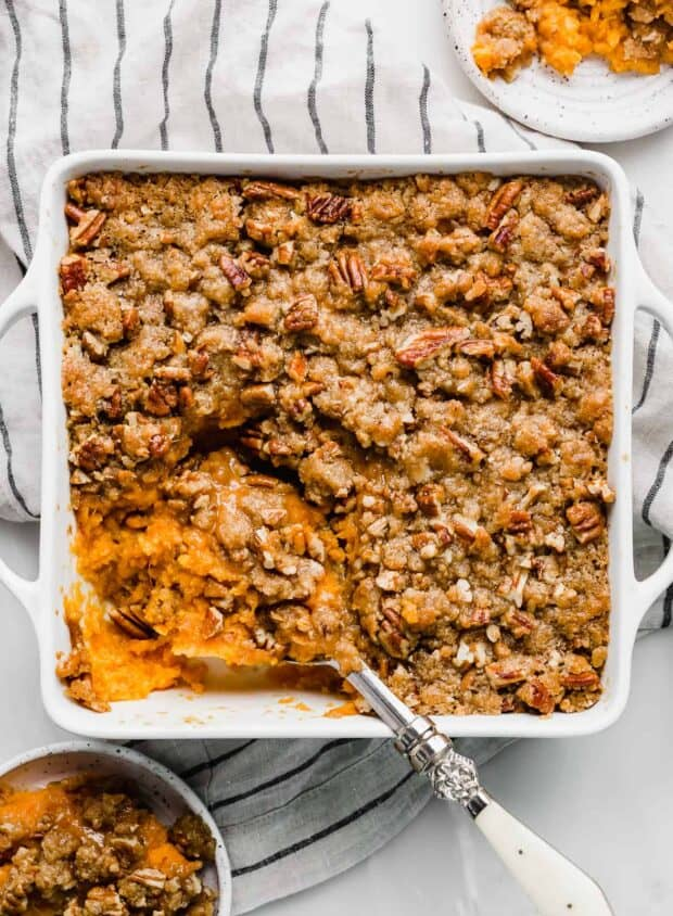 A large serving spoon scooping into a sweet potato casserole.