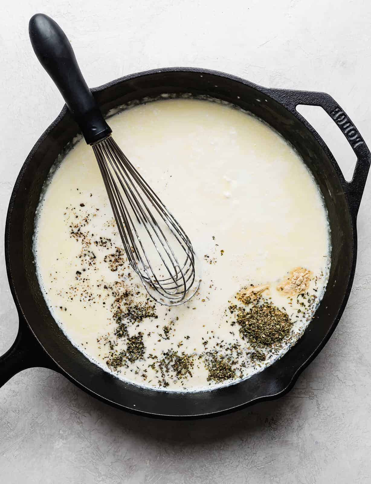 A skillet with cream and seasonings to make Fettuccine Alfredo.