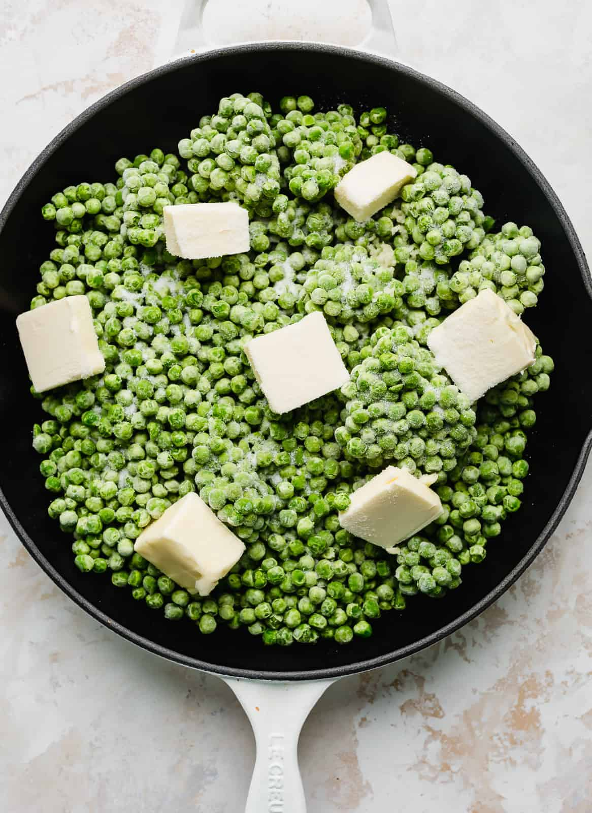 Frozen peas, cubed butter, sugar, and minced garlic in a skillet.