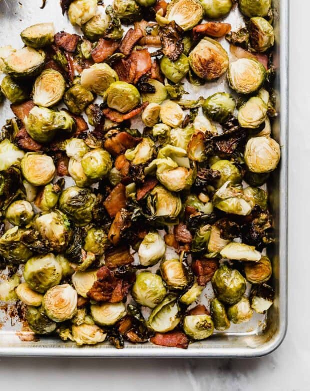 roasted Brussels sprouts and crispy bacon on a baking sheet.