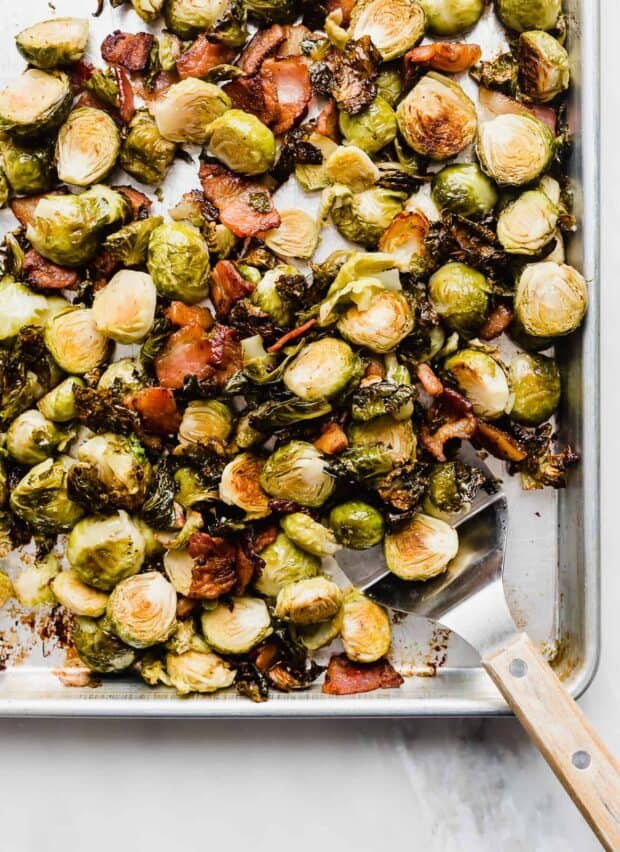 Roasted Brussels Sprouts with Bacon on a baking sheet, with a metal spatula scooping up some of the food.