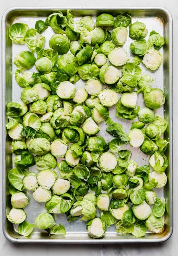 Trimmed and halved Brussels sprouts spread out on a baking sheet.