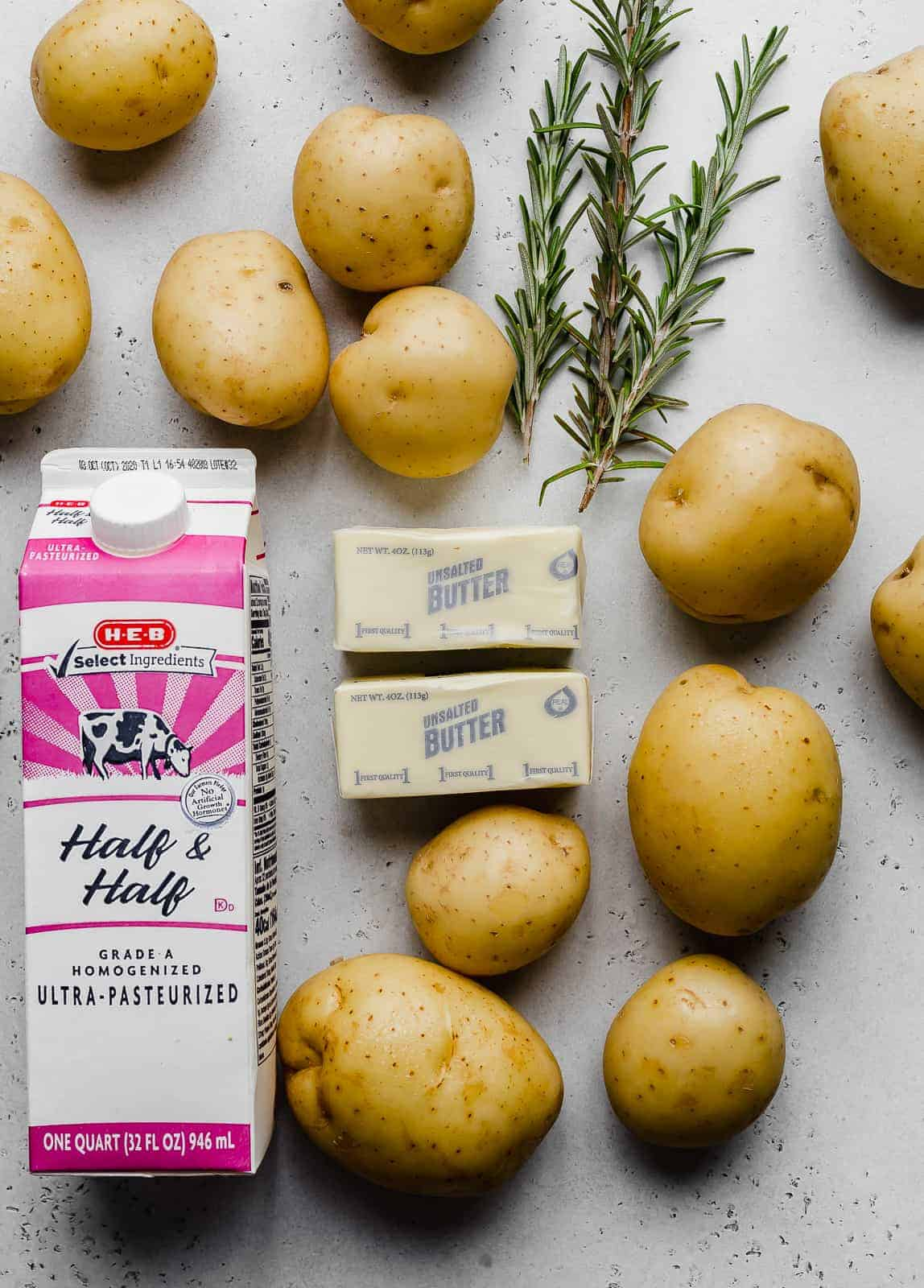 Ingredients used to make mashed potatoes: potatoes, half and half, butter, and rosemary against a grey background.