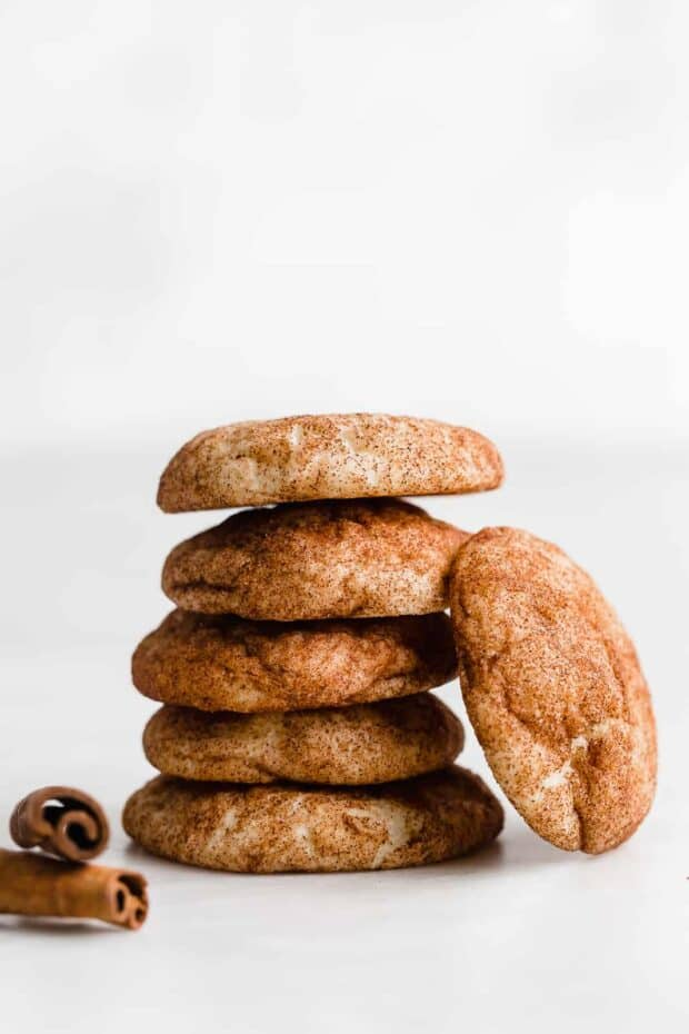 Five snickerdoodles stacked on top of one another, against a white background.