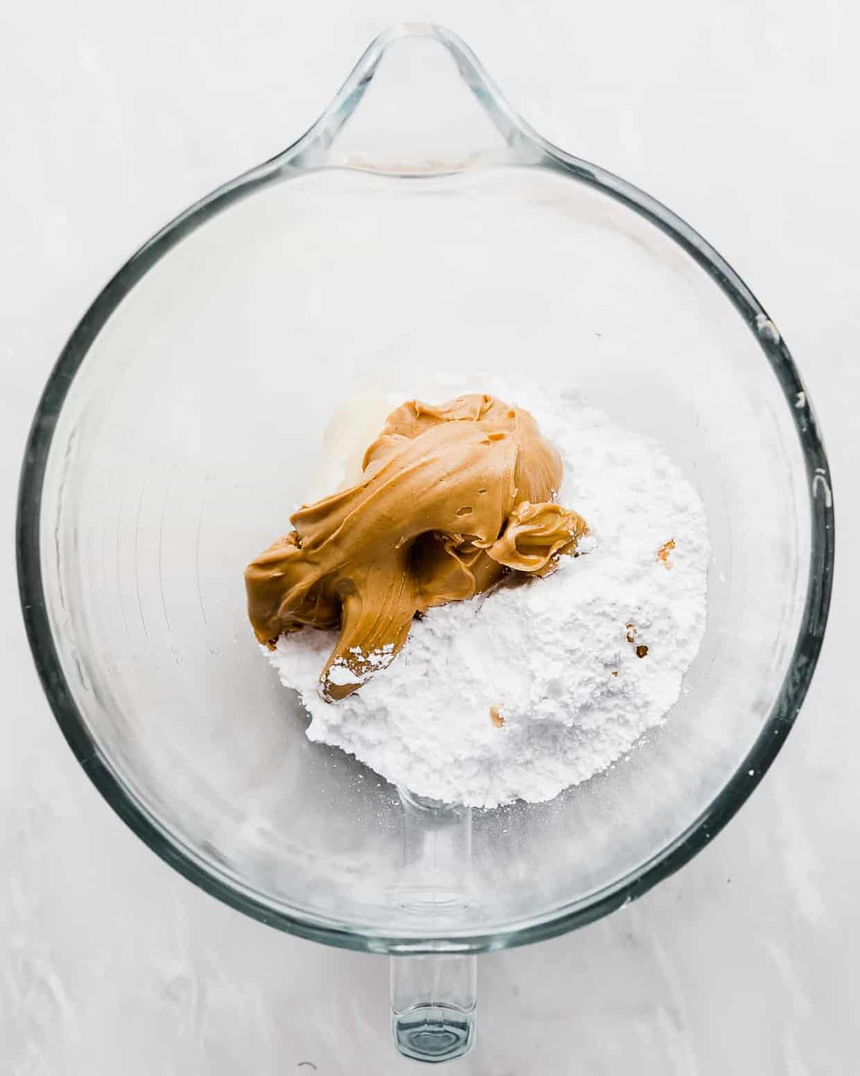 A glass bowl with peanut butter and powdered sugar in it.