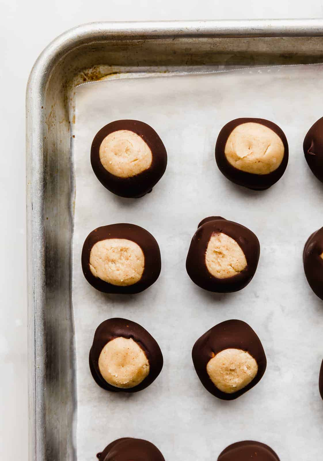 Chocolate dipped buckeyes lined up on a parchment lined baking sheet.