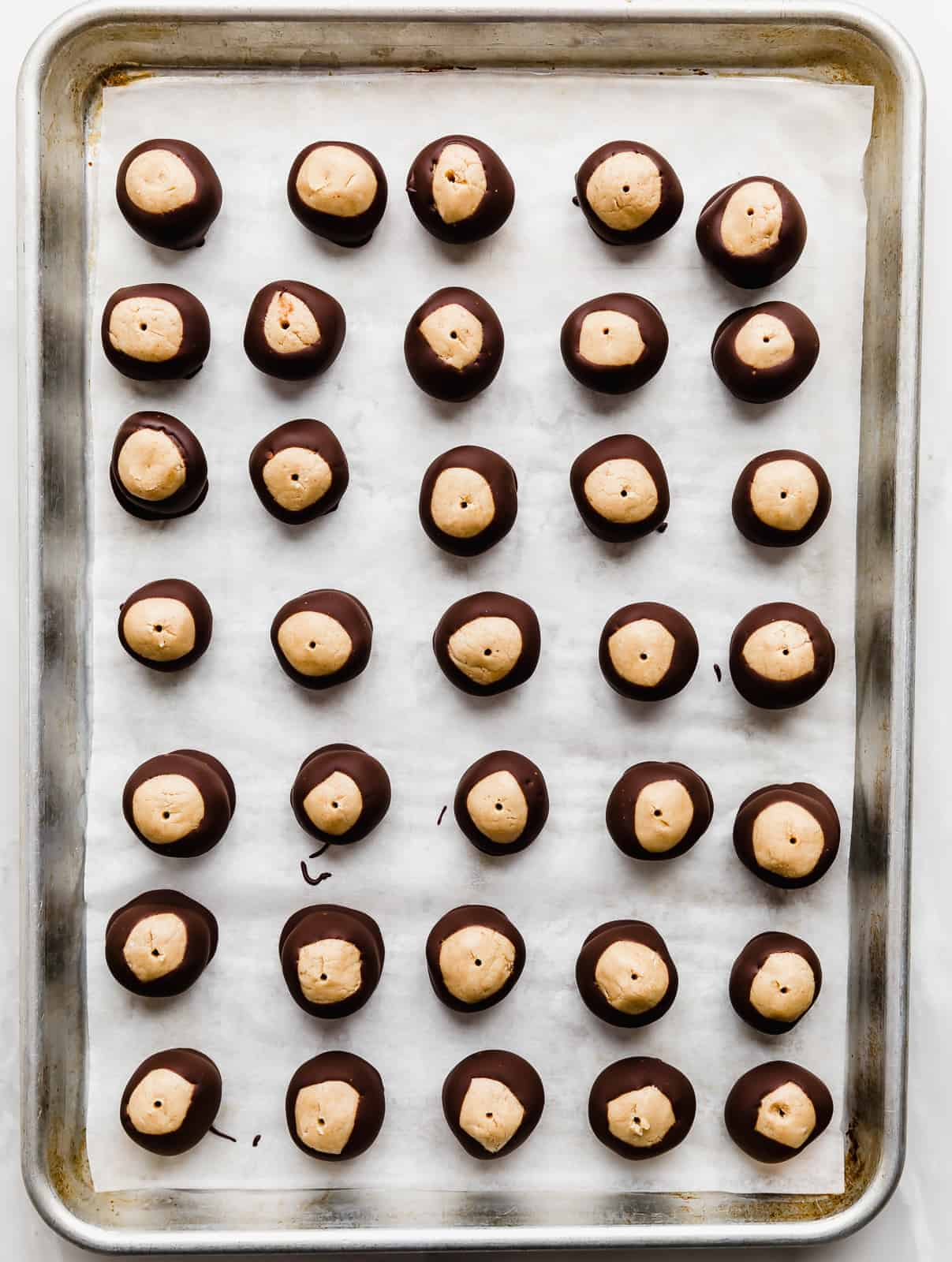 Chocolate dipped buckeyes on a baking sheet.