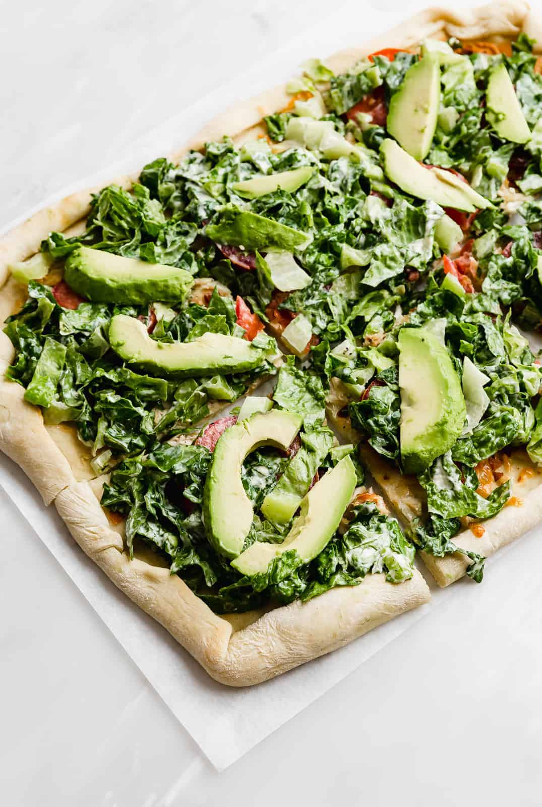 A CPK Club Pizza topped with lettuce and avocado, against a white background.