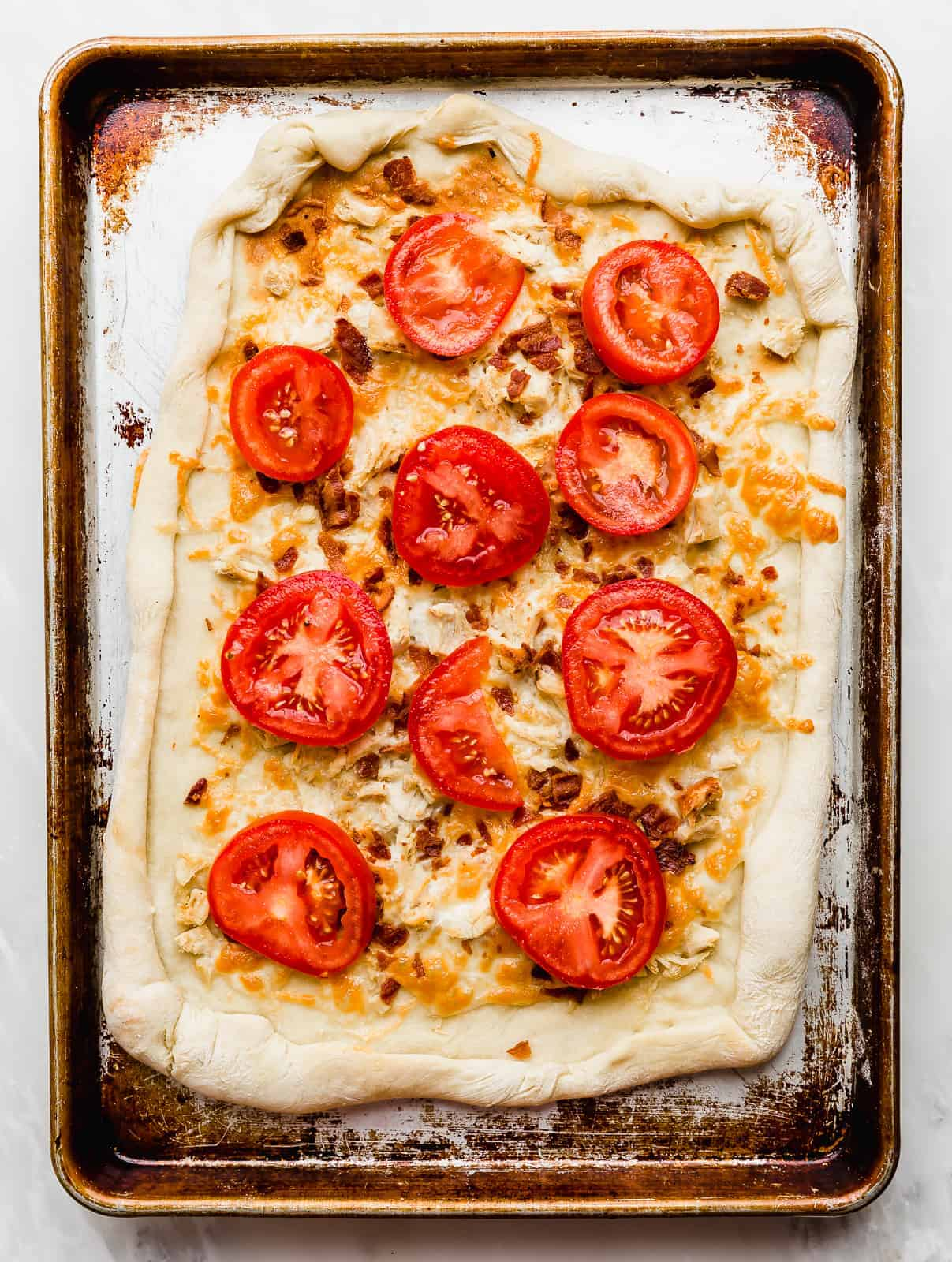 Tomato slices on top of a rectangular baked pizza dough.