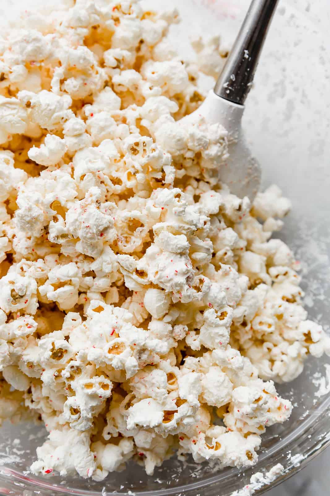 A close up photo of popped popcorn covered in white chocolate and crushed candy canes.
