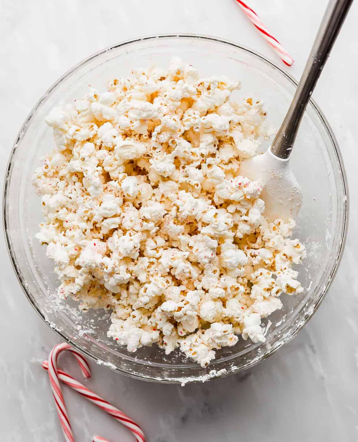 A large glass bowl full of popped popcorn covered in white chocolate and crushed candy canes.