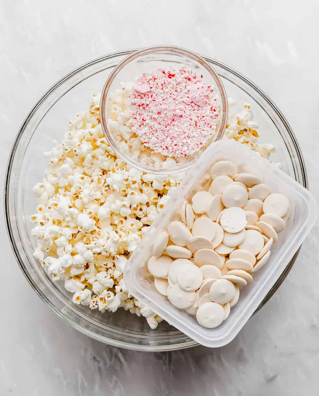 A large bowl of popcorn, a bowl of white candy melts, and a bowl of crushed candy canes.