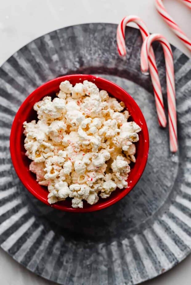 A bowl of popcorn on a metal plate.