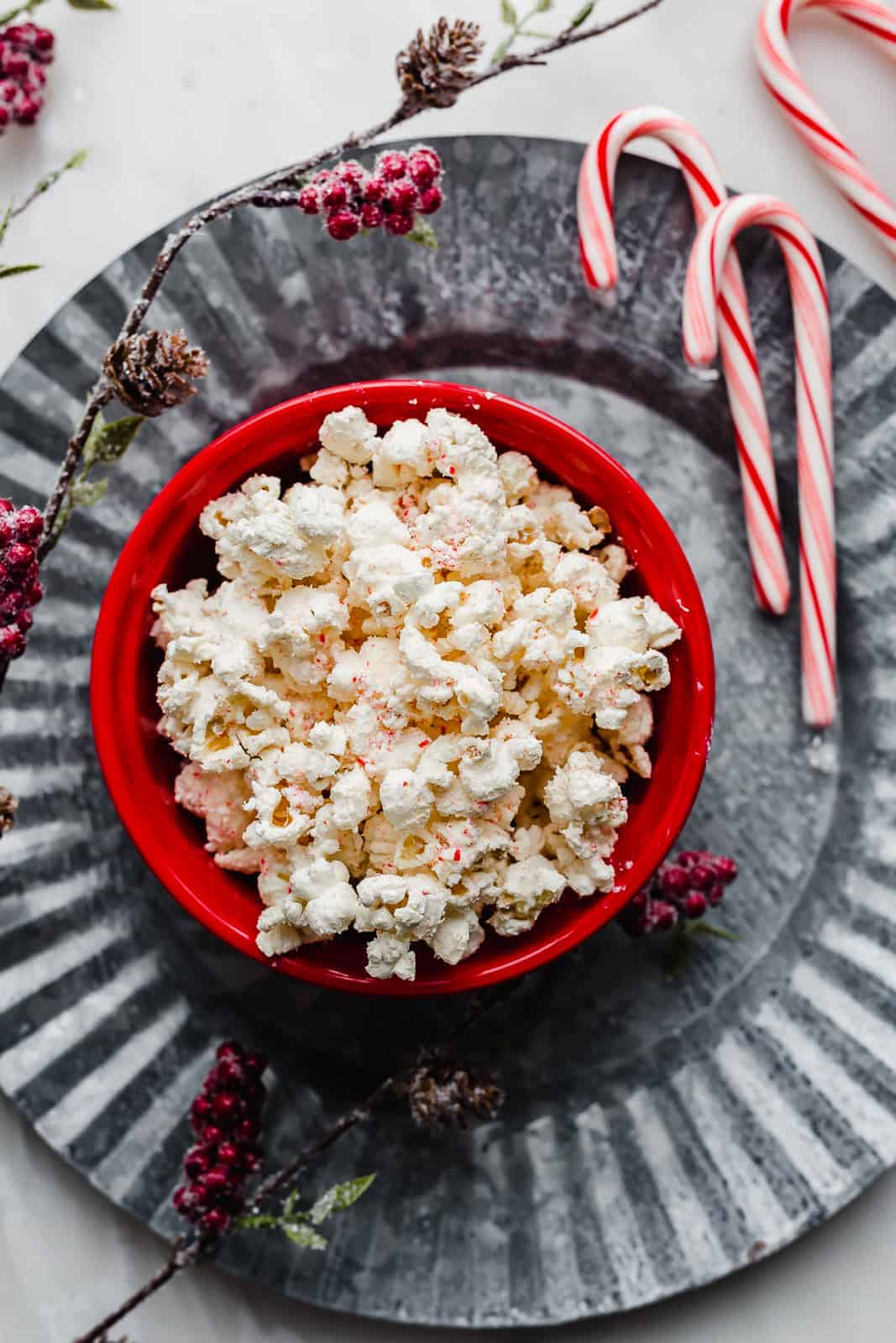 Popcorn in a red bowl against a metal gray background.