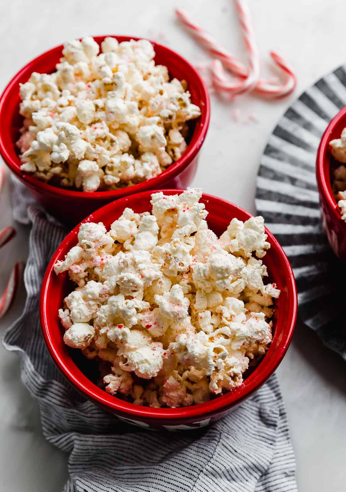 Two red bowls full of popped popcorn.