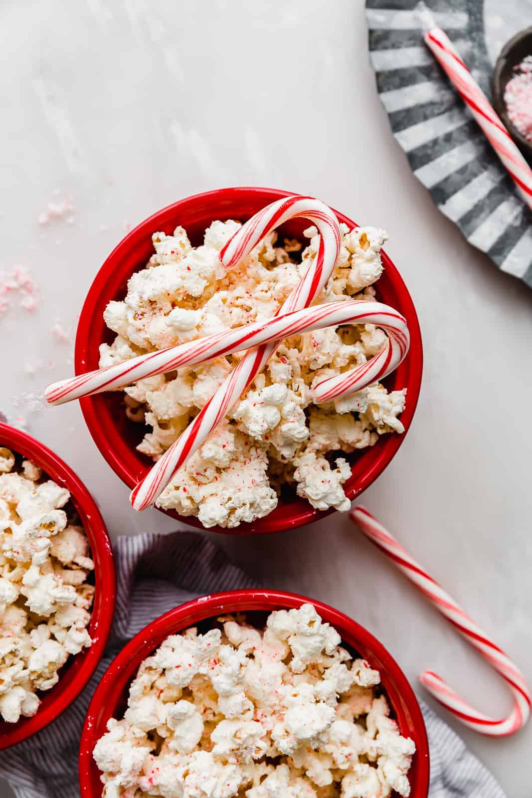 Candy Cane Popcorn in a red bowl with two candy canes on top of the popcorn.