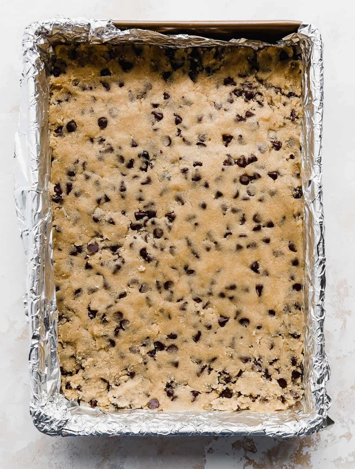 A 9x13 inch baking dish with chocolate chip cookie dough pressed into the pan.