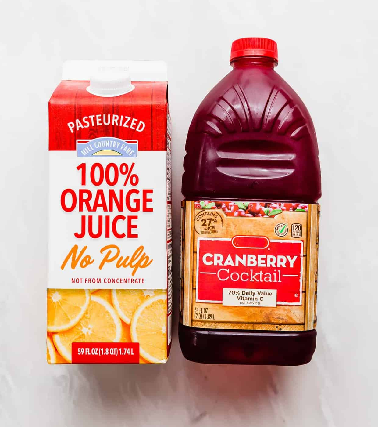 A carton of orange juice and cranberry juice cocktail against a white background.