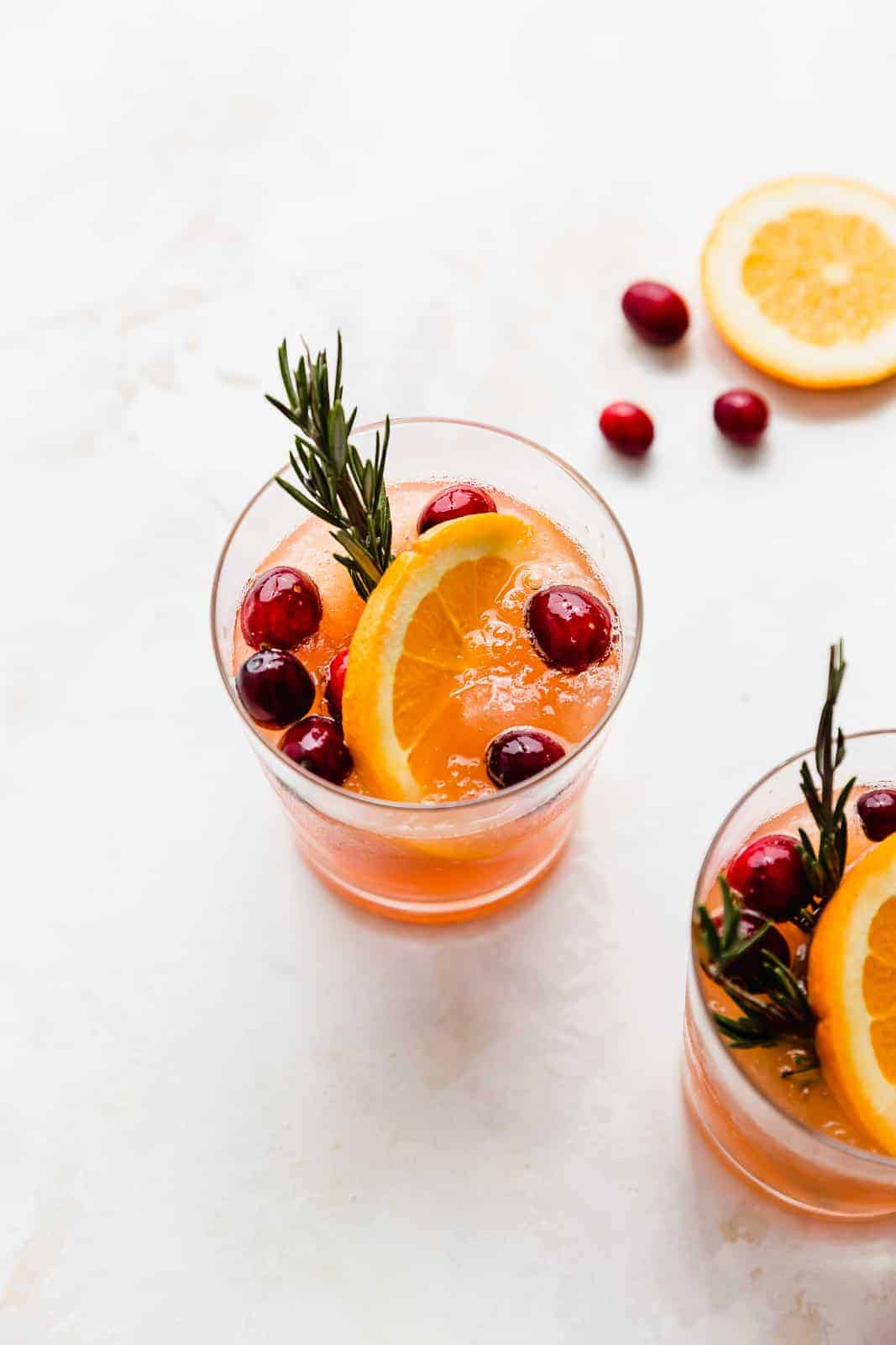 A glass full of slushy Christmas cranberry punch garnished with an orange slice and fresh cranberries.