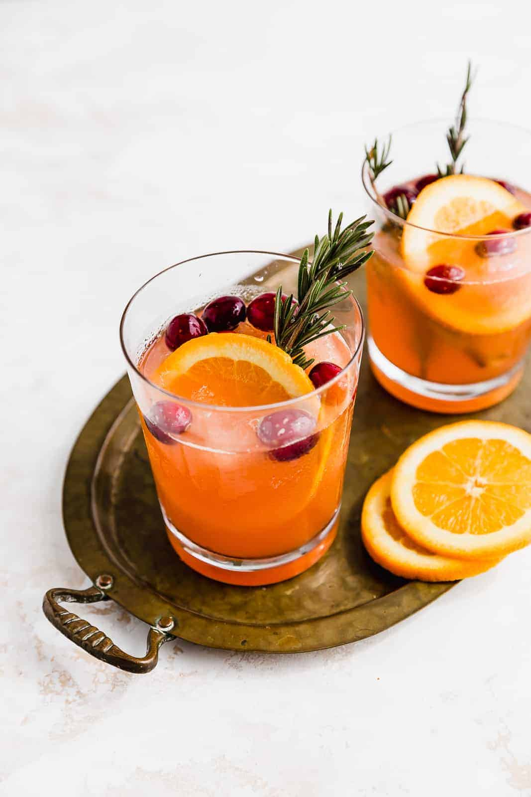 Two glasses of Christmas Cranberry Slush Punch on a bronze tray.