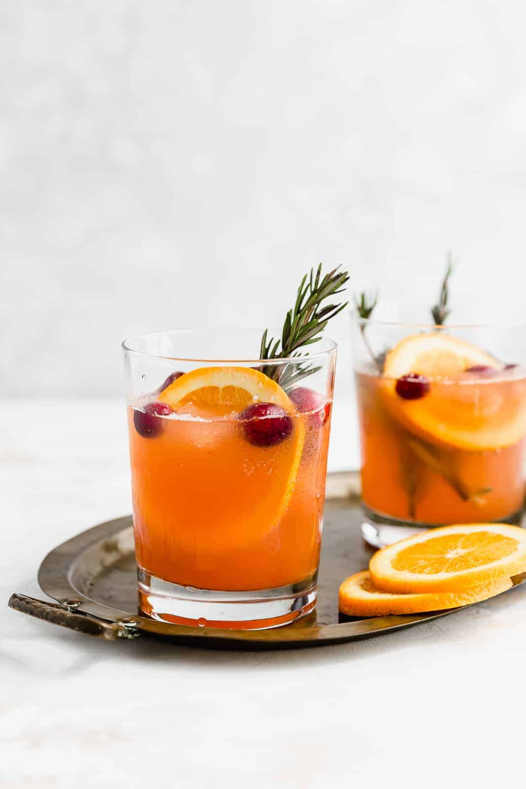 Two glasses of Christmas Slush Punch garnished with rosemary, cranberries, and an orange slice.