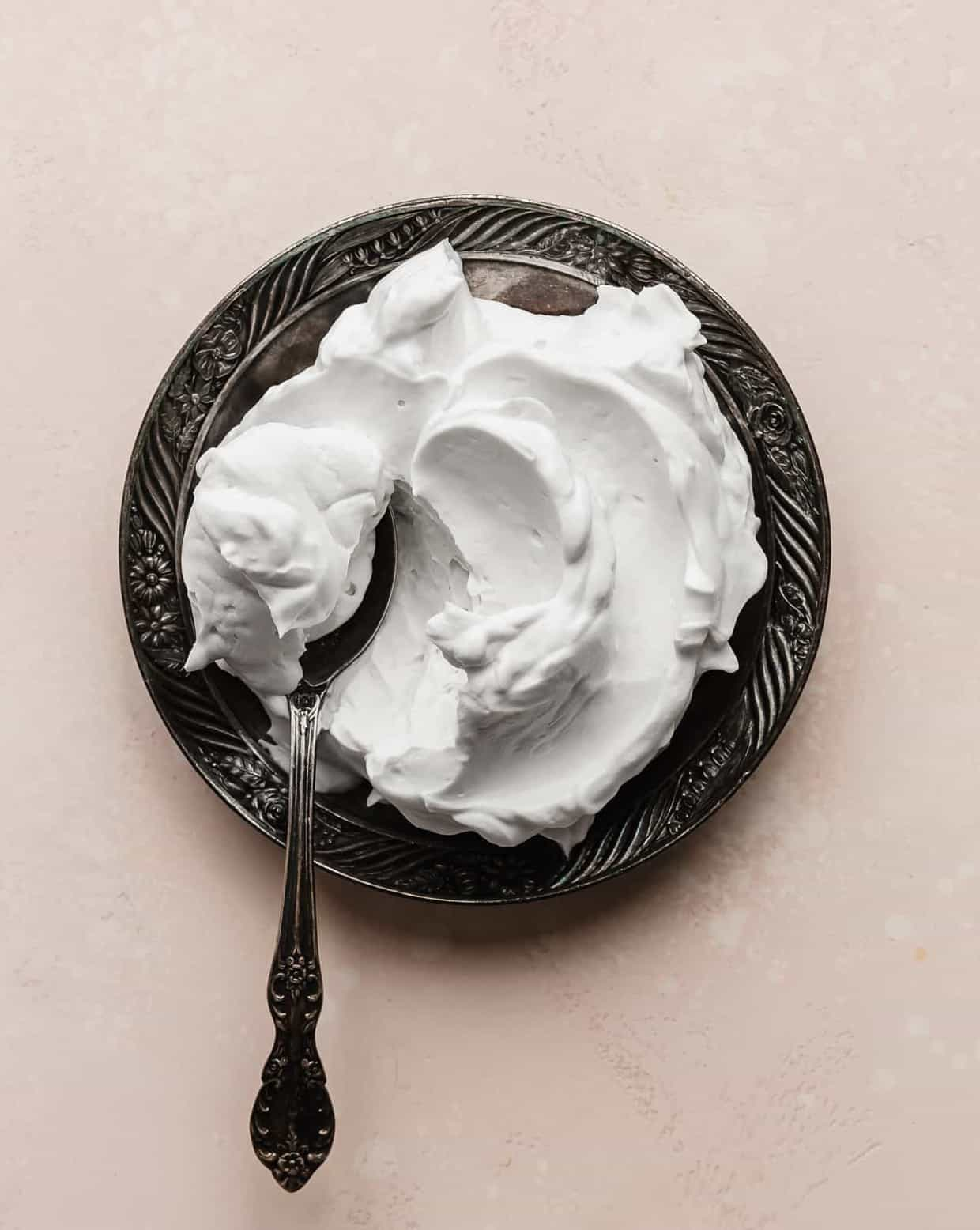 A plate full of pillowy Coconut Whipped Cream against a soft pink background.