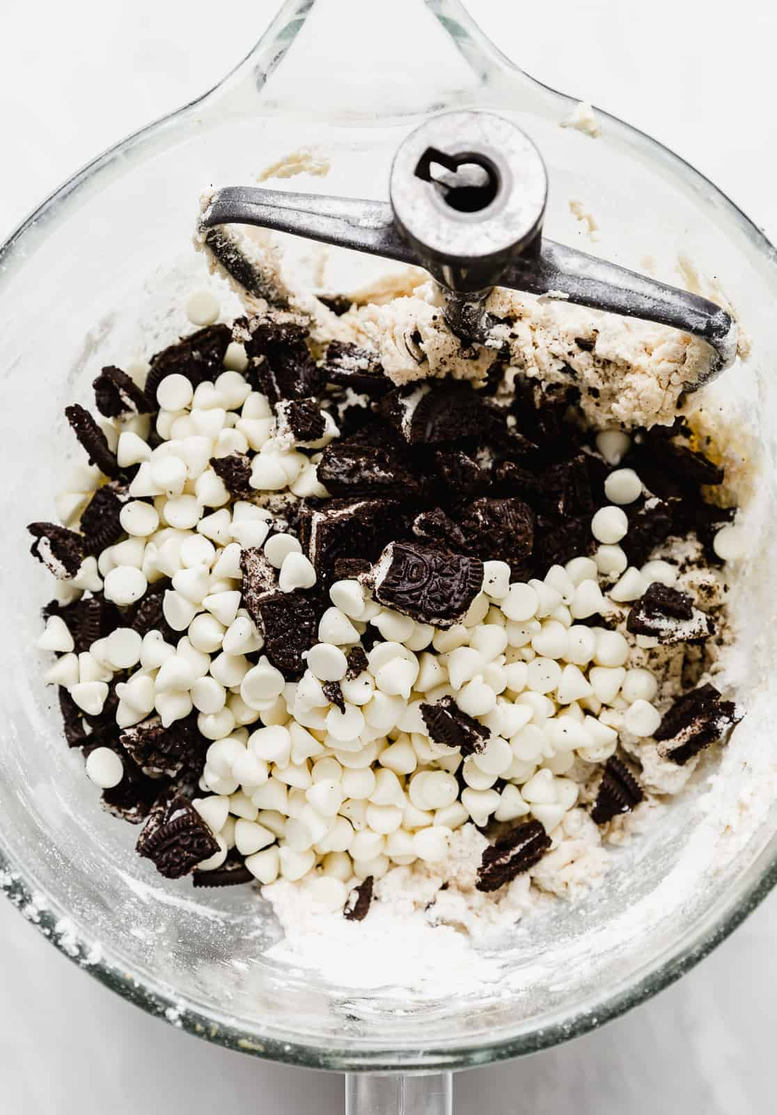 A large glass bowl full of Cookies and Cream Cookie dough batter with white chocolate chips and chopped Oreo's on top.
