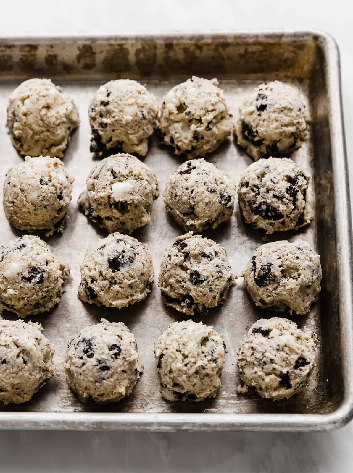 Oreo and white chocolate chip loaded cookies and cream cookies scooped into cookie dough balls, sitting on a baking sheet.