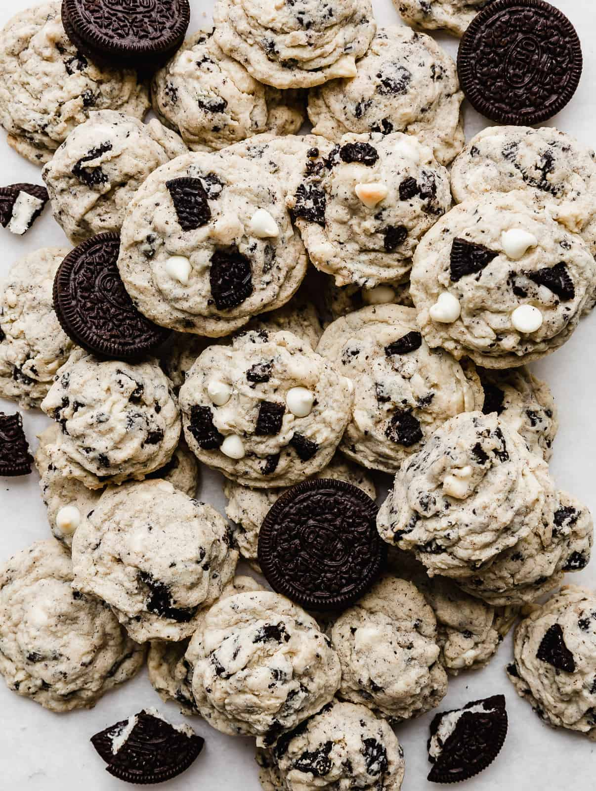 A pile of Cookies and Cream Cookies with Oreo's amongst the pile.