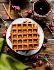 Square gingerbread waffles on a white plate with a green towel to the side.