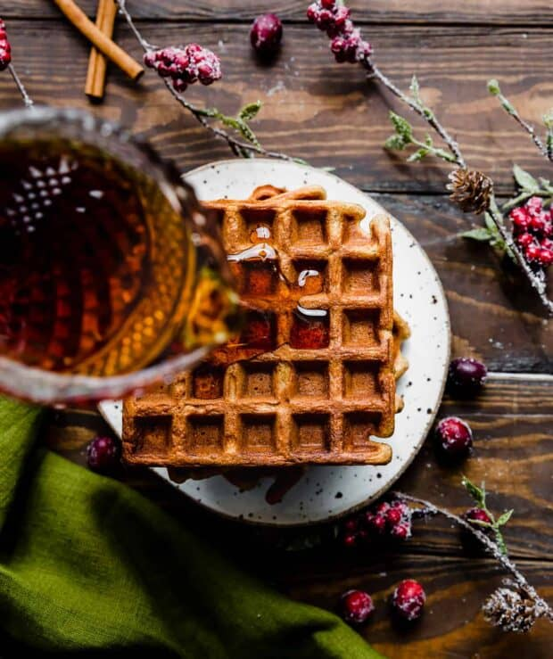 Syrup being poured over gingerbread waffles.