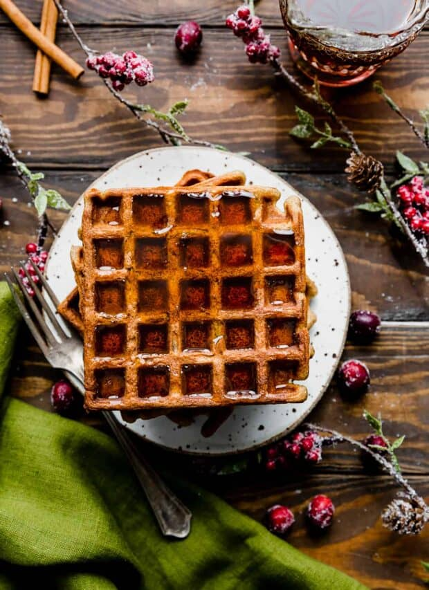 Gingerbread Waffles on a white plate against a wooden background.
